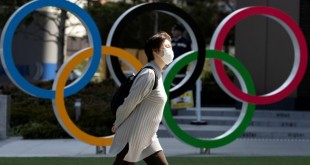 FILE PHOTO: A woman wearing a protective face mask, following an outbreak of the coronavirus disease (COVID-19), walks past the Olympic rings in front of the Japan Olympics Museum in Tokyo