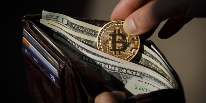 BERLIN, GERMANY - AUGUST 14: A hand puts a Bitcoin in a wallet, filled with dollar bills on August 14, 2015, in Berlin, Germany. (Photo by Thomas Trutschel/Photothek via Getty Images)